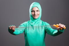 Happy beautiful muslim woman in green hijab or islamic sport wear standing, holding and showing jump rope and looking at camera w. Ith toothy smile. indoor royalty free stock photography