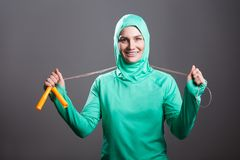 Happy beautiful muslim woman in green hijab or islamic sport wear standing, holding jump rope and looking at camera with toothy s. Mile. indoor studio shot royalty free stock photos