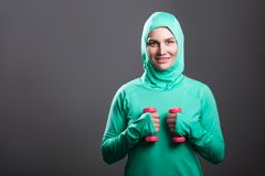 Happy beautiful muslim woman in green hijab or islamic sportswear standing, holding red dumbbells and looking at camera with toot. Hy smile. indoor studio shot royalty free stock image