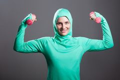 Happy beautiful muslim woman in green hijab or islamic sportswear standing, holding red dumbbells, raised arms, looking at camera. And toothy smile. indoor stock photography