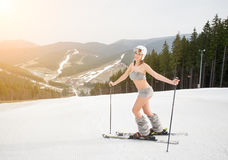 Happy beautiful naked girl skier posing on the snowy slope with ski equipment Stock Photography