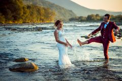 Happy beautiful newlywed couple having fun in the water while the groom is splashing water on his lovely bride. Beautiful landscape during the sunset Royalty Free Stock Photography