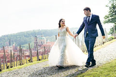 Happy beautiful newlyweds are holding hands and walking along the pavements at the background of the Prague panorama. Royalty Free Stock Images