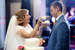 Happy beautiful  newlyweds taste cake in restaurant. A Stock Photos