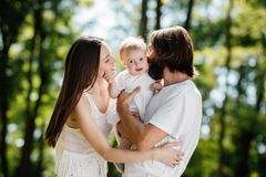 Happy beautiful parents dressed in the white casual clothes spending sunny day in the park with there little daughter. stock photos