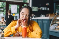 Happy beautiful plus size woman smiling and drinking healthy smoothie in cafe royalty free stock photography