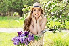 Happy and beautiful. Portrait of attractive young woman in hat and dress looking away and smiling while sitting on retro bike. Attractive girl on an old Stock Images