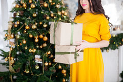 Happy beautiful pregnant woman holding gifts near a Christmas tr Stock Photography
