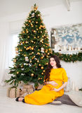 Happy beautiful pregnant woman sitting near the Christmas tree Royalty Free Stock Image