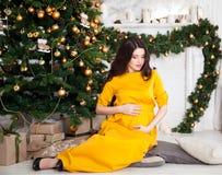 Happy beautiful pregnant woman sitting near the Christmas tree Stock Photos