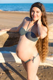 Happy beautiful pregnant woman in swimsuit relaxing at beach Royalty Free Stock Image