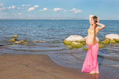 Happy beautiful pregnant woman in swimsuit walking royalty free stock photography