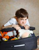 Happy beautiful preteen boy gather case before the trip to the Stock Images