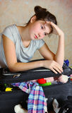 Happy beautiful preteen girl pack coffer. Happy beautiful preteen girl packing coffer before the trip to the seaside land Royalty Free Stock Photos