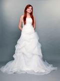 Happy beautiful red haired bride on gray background Royalty Free Stock Image