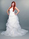 Happy beautiful red haired bride on gray background Stock Image