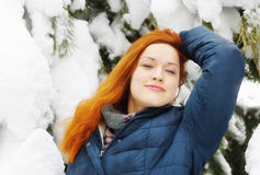 Happy beautiful redhead girl relaxes in snowy pine forest Royalty Free Stock Images