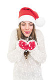Happy beautiful Santa girl holding and blowing snow Royalty Free Stock Photography