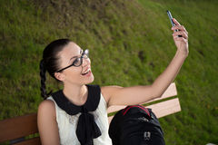 Happy beautiful school girl making selfie photo on smartphone in Royalty Free Stock Images