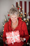 Happy beautiful senior with a Christmas gift Stock Photos