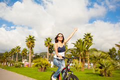 Happy beautiful sexy girl woman riding bicycle with raised hands Royalty Free Stock Images