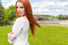 Happy beautiful red-haired girl in a white dress walks in the park Stock Images