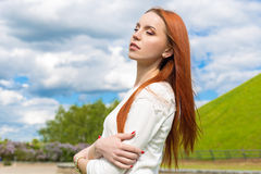 Happy beautiful sexy red-haired girl in a white dress walks in the park Stock Images