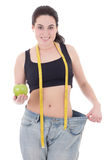 Happy beautiful slim woman in big jeans with apple and measuring. Tape isolated on white background Royalty Free Stock Photo
