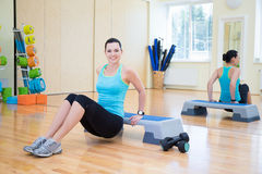 Happy beautiful slim woman working out with stepper in gym Stock Photos