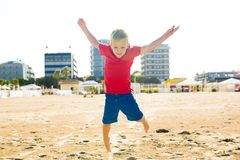Happy beautiful smiling child jumping at the sand beach, hands up Stock Image