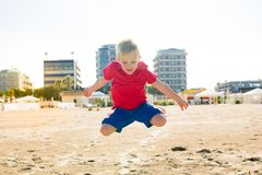 Happy beautiful smiling little boy jump at the sand beach Stock Photo