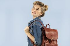 Beautiful student girl in a denim jacket with a backpack on her shoulders in the studio on a blue background. The concept of royalty free stock photo