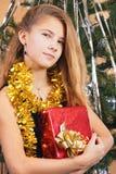 A happy beautiful teen girl hugs her gift. Near a Christmas tree Royalty Free Stock Photo