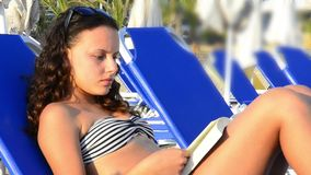 Happy Beautiful Teen Girl Sunbathing & reading book at the beach HD. stock video footage