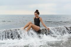 Happy beautiful teenage girl at sea. A wave rolls over the rocks royalty free stock photo