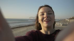 Happy beautiful teenager girl taking selfie using smartphone on the beach while spinning and enjoying nature in slow motion stock video footage