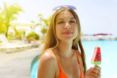 Happy beautiful tourist eating popsicle ice pop in form of watermelon slice and looking at  camera. Summer holidays concept. Happy beautiful tourist eating royalty free stock image