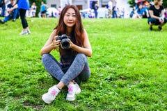 Happy beautiful traveler asian woman with camera. Young joyful asian women using camera to making photo during city tour. royalty free stock photography