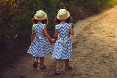Happy twin sisters children. Girls sister in a park , walking on the road, holding hands. Sunlight and view from back. Stock Images