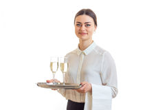 Happy beautiful waitress holding a tray with glasses of wine and smiling stock photography
