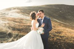 Happy beautiful wedding couple bride and groom at wedding day outdoors on the mountains rock. Happy marriage couple. Outdoors on nature, soft sunny lights Royalty Free Stock Images