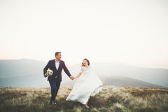 Happy beautiful wedding couple bride and groom at wedding day outdoors on the mountains rock. Happy marriage couple Royalty Free Stock Images