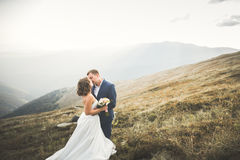 Happy beautiful wedding couple bride and groom at wedding day outdoors on the mountains rock. Happy marriage couple Stock Image