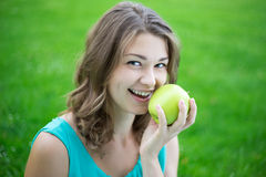 Happy beautiful woman with apple in summer park Stock Photo