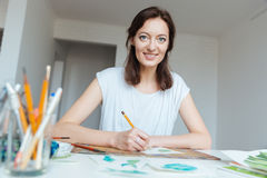 Happy beautiful woman artist drawing by pencil at the table Stock Images