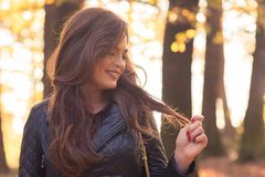 Happy beautiful woman in autumn park. Or fall forest posing relaxed royalty free stock photo