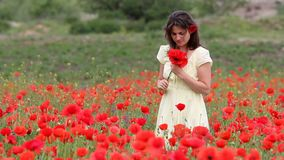 Happy beautiful woman in blossom field arrange a poppy flower in hair, smiling. Full HD stock video footage