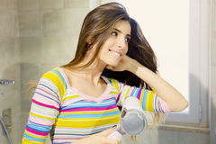 Happy beautiful woman blow drying long hair in bathroom Stock Images