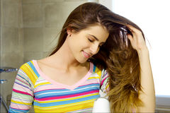 Happy beautiful woman blow drying long hair in bathroom moving with hand Stock Photos
