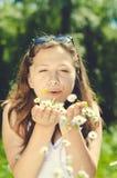 Happy beautiful woman blowing dandelion over Stock Photo
